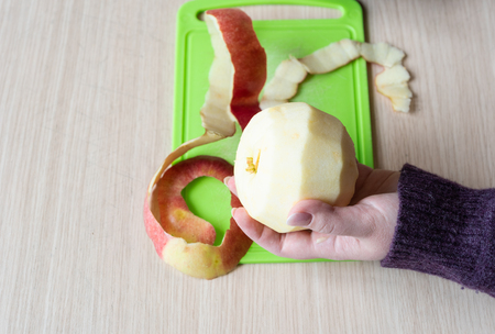 Peeled apple in girl's hand. Apple peel on a green cutting board. Close up