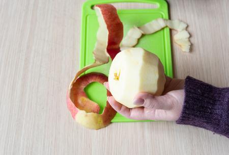 Peeled apple in girl's hand. Apple peel on a green cutting board. Close up Фото со стока