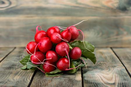 Fresh radish on wooden background. Bunch of radish with leaves on a wooden background. Copy space. Close up