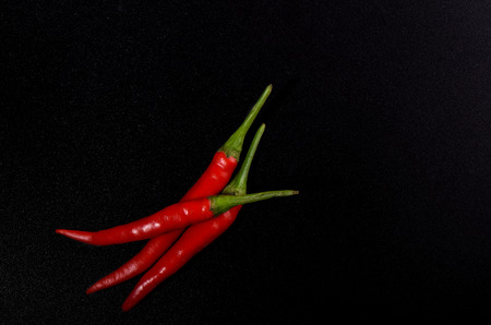 Pods of red hot pepper isolated on black color background. Copy space