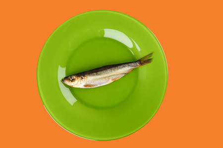Cold smoked Baltic herring on an green plate isolated on orange background. Smoked Baltic herring smoked until golden brown. Top view Stock Photo