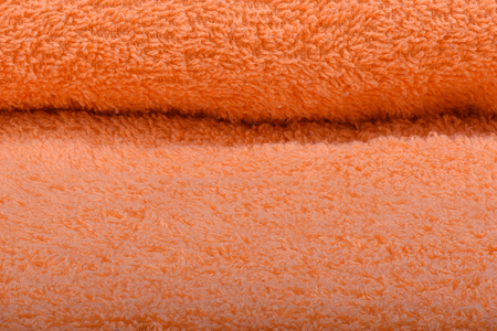 Orange terry towel. The texture of the cloth towels. Close up