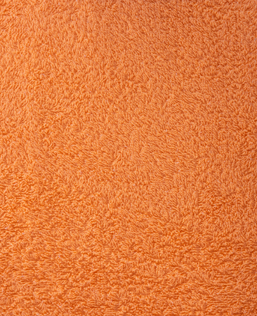 The texture of the fabric is orange terry towel. Terry cloth as a background.