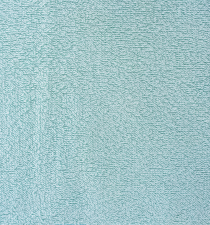 The texture of the fabric is light blue terry towel. Terry cloth as a background.