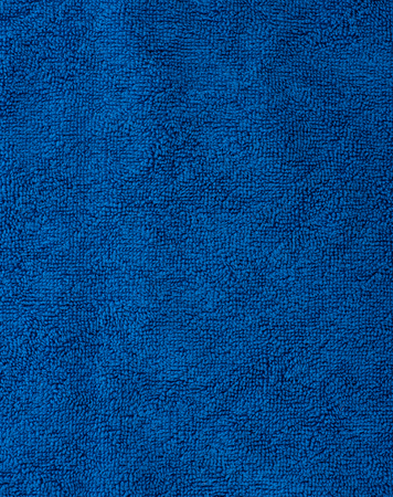 The texture of the fabric is blue terry towel. Terry cloth as a background. Stock Photo
