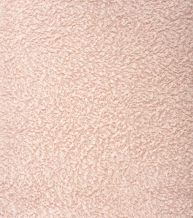 The texture of the fabric is light pink terry towel. Terry cloth as a background.