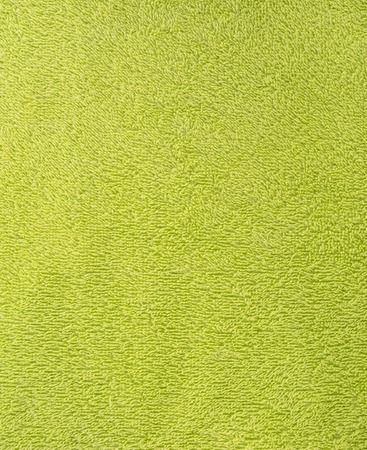 The texture of the fabric is green terry towel. Terry cloth as a background.