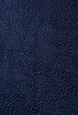 The texture of the fabric is dark blue terry towel. Terry cloth as a background.