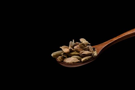 Cardamom seeds on a wooden spoon over black background. Cardamom boxes are the seeds of an Indian tree from the ginger family. Copy space.