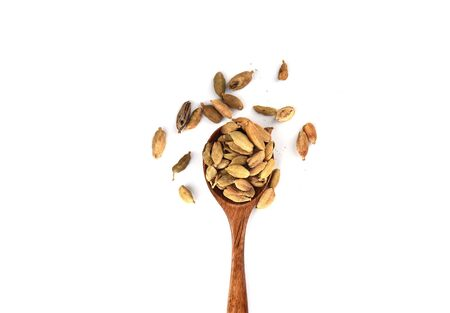 Cardamom seeds on a wooden spoon isolated on white background. Cardamom boxes are the seeds of an Indian tree from the ginger family. Copy space. Top view