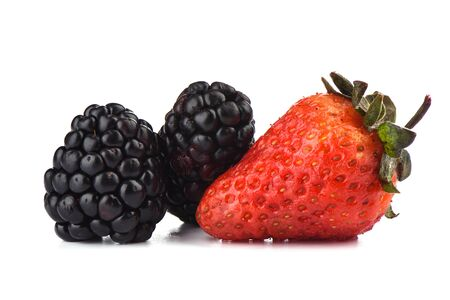 Two ripe blackberries and one strawberry over white background. Macro shot. Copy space