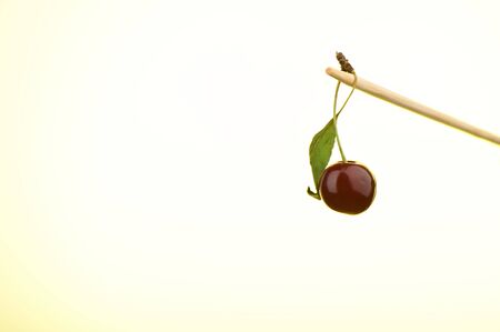 Ripe cherry on a stick with a yellow backlit background. Copy space. Stok Fotoğraf