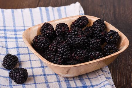 A few blackberries in a wooden bowl. Blackberry on a kitchen towel on a wooden table. Rustic style Stock Photo
