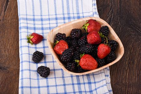 A few blackberries and strawberries in a wooden bowl. Blackberries and strawberries on a kitchen towel on a wooden table. Rustic style. Stock Photo
