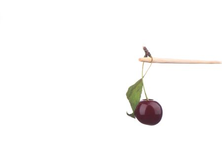 Ripe cherry on a stick over a white background. Copy space. Close up