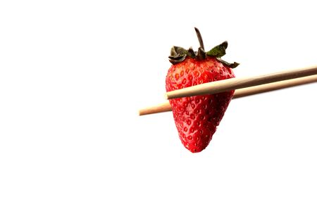 Chopsticks with ripe strawberry over white background. Copy space