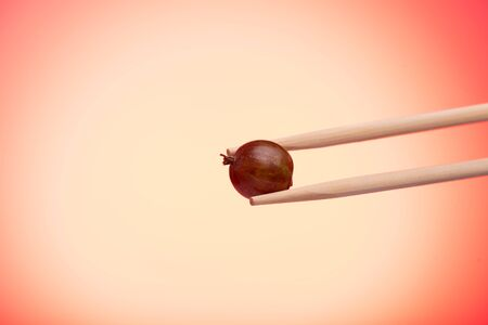 Wooden chopsticks ripe red berry gooseberry. Copy space. Red lights. Macro shot
