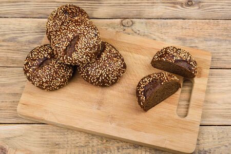 Malt bread with sesame on a cutting board and a wooden table. Sliced bread. Rustic style.