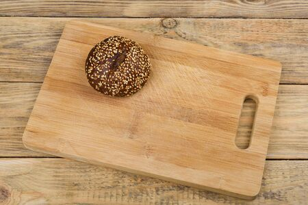 Malt bread with sesame seeds on a cutting board over a wooden table. Rustic style.
