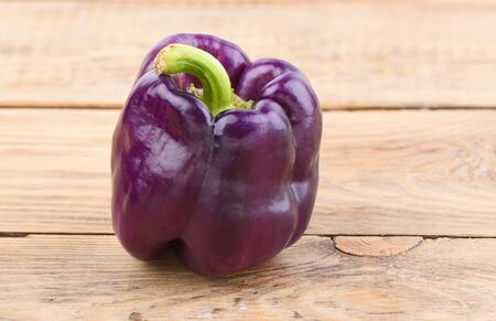 Fresh purple bell pepper on a wooden table. Rustic style. Close up.