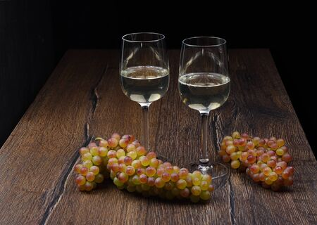 Two glasses of white wine and a bunch of grapes on wooden table.