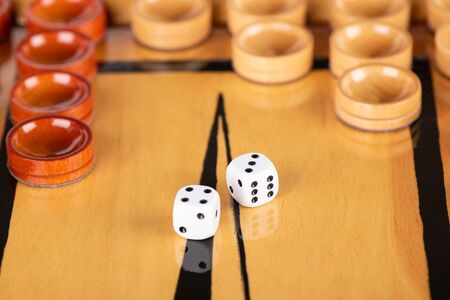 Dice and checkers on a wooden backgammon board. Game dice are reflected on the surface of the backgammon board. Close up. On dice 4 3