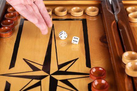 A hand throws white dice on a backgammon board. close up.