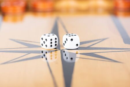 Dice and checkers on a wooden backgammon board. Game dice are reflected on the surface of the backgammon board. Close up. Stock Photo
