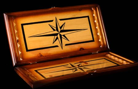 Opened backgammon board over a dark background. A beautiful board for an old backgammon game.