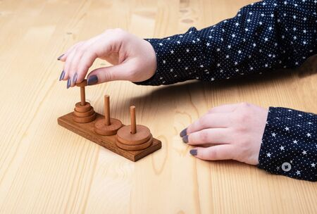 A girl is trying to assemble a puzzle tower of hanoi. Dark manicure. Puzzle concept.