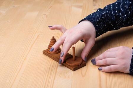 Girl plays puzzle tower of hanoi. Dark manicure. Puzzle concept. 写真素材
