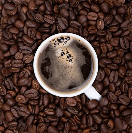 Coffee cup with black freshly brewed coffee among coffee beans. Fragrant coffee beans.