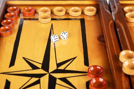 Dice and checkers on a wooden backgammon board. Game dice are reflected on the surface of the backgammon board. Close up. On dice lucky 5 5. Board games concept.
