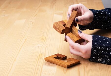 The girl is trying to solve the constructor puzzle oblique knot. Dark manicure on nails. Puzzle concept. Copy space