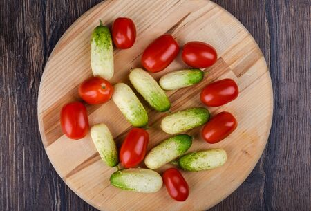 Top view. Fresh ripe little cucumbers and cherry tomatoes on a wooden cutting board. Rustic style. Stock Photo - 133322649