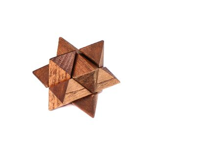 Assembled wooden puzzle star-shaped dodecahedron. Twelve-sided small star dodecahedron isolated on white background. Copy space. Puzzle concept.