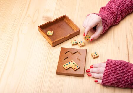 Girl is trying to assemble a mosaic puzzle. Bright manicure on fingernails. Puzzles from the category edge matching puzzle.