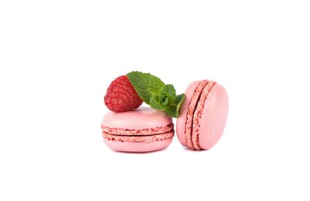 Two pink macaroon with raspberry and mint leaves isolated on a white background. 写真素材