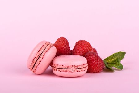 Two pink macaroon with raspberries and mint leaves isolated on a pink background.