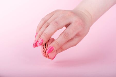 Tasty pink macaroon in female hand over pink background.