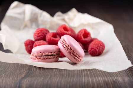 Pink macaroons with raspberries on a sheet of paper over a wooden background.