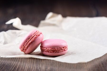 Two pink macaroons on a sheet of paper over a wooden background.
