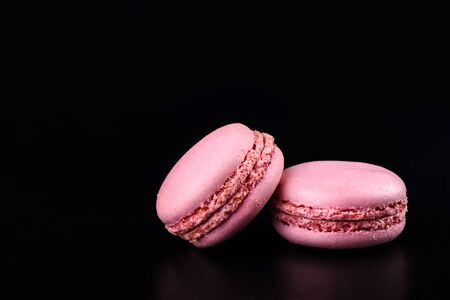 Two pink macaroons on a black background.