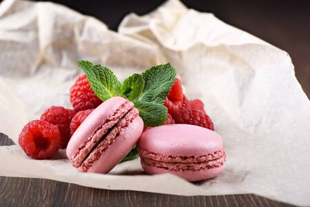 Pink macaroons with raspberries and mint leaves on a sheet of paper over a wooden background.