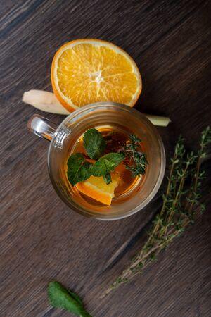 Glass mug with vitamin tea. Vitamin tea ingredients on a wooden table. Фото со стока