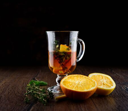 Vitamin tea with orange, lemon, mint, thyme and lemon grass. Vitamin tea ingredients on a wooden table. Prevention against colds. Healthy lifestyle. Фото со стока