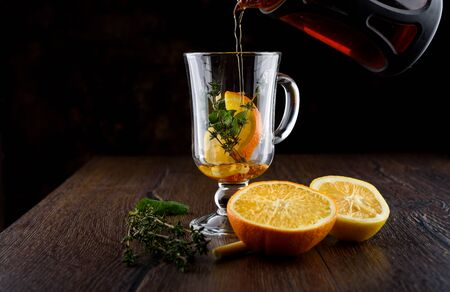 Making vitamin tea with orange, lemon, mint, thyme and lemon grass. Vitamin tea ingredients on a wooden table. Prevention of colds. Healthy lifestyle. Фото со стока