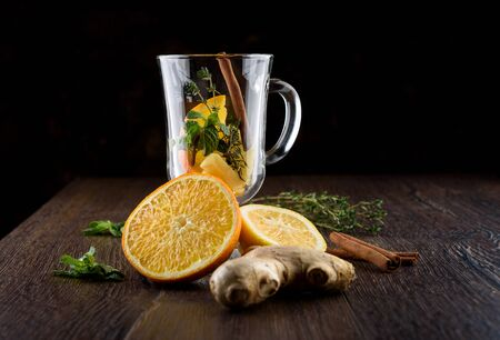 Ingredients for making vitamin tea with orange, lemon, mint, thyme, ginger root and cinnamon. Prevention of colds. Healthy lifestyle.