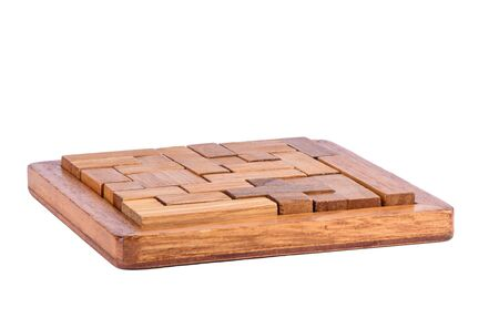 Three-dimensional wooden pentamino board game on a white background. Board games concept. Copy space.