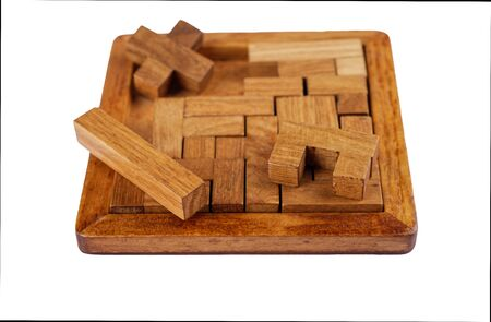 Selective focus. Three-dimensional wooden pentamino board game on a white background. Board games concept. Copy space.
